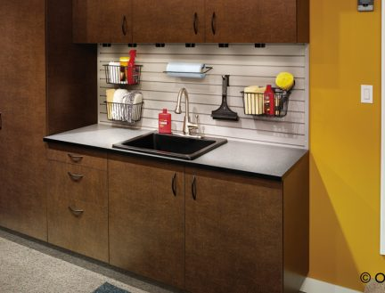 brown wood cabinets with black countertop and peg board